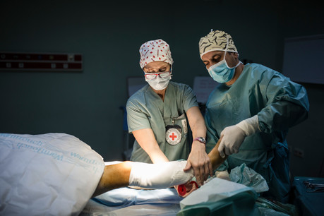Red Cross workers perform surgery in a Iraq hospital