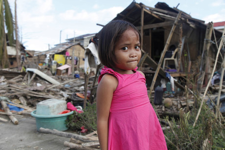 A little girl stands in a damaged area after Typhoon Haiyan