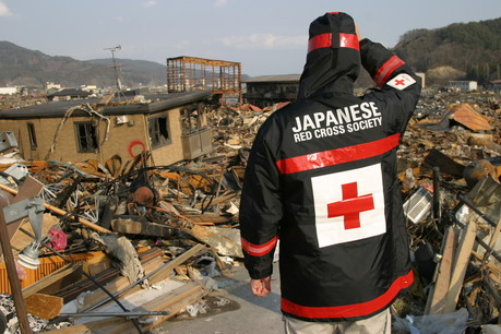 A Japanese Red Cross worker looks at damage from the earthquake