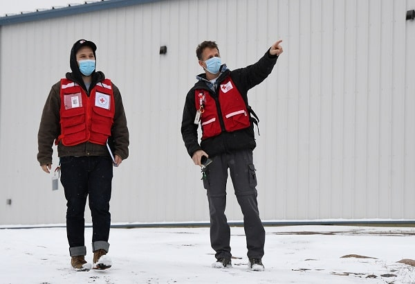 Two team members from Canadian Red Cross standing outside a building with masks on.