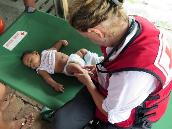 Doctor examining a baby with a rash at a mobile clinic