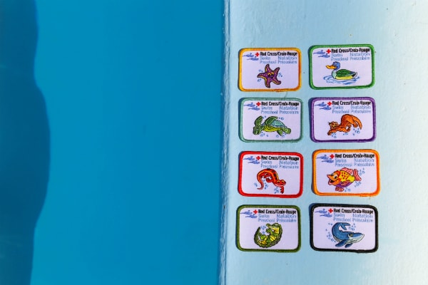 Photo of Red Cross Preschool Swim Badges by a pool