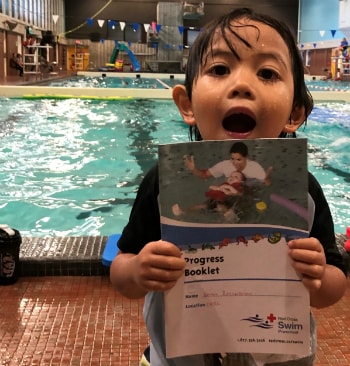 Kai smiling holding his Red Cross swim progress book infront of the pool