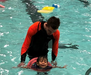 Kai swimming in the water with his swimming instructor
