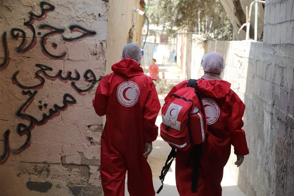 Members of Palestinian Red Crescent Society walking through an alleyway
