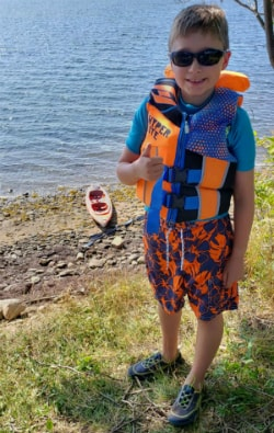 Xavier standing infront of water with lifejacket on