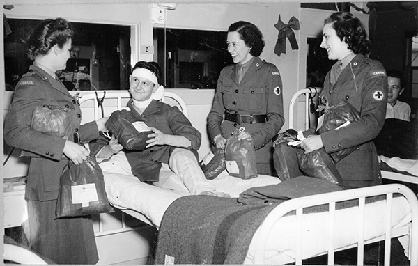 "Three CRCC Welfare Officers visit a convalescing soldier overseas (ca. 1943-45) while distributing ""ditty bags"" on a hospital ward."