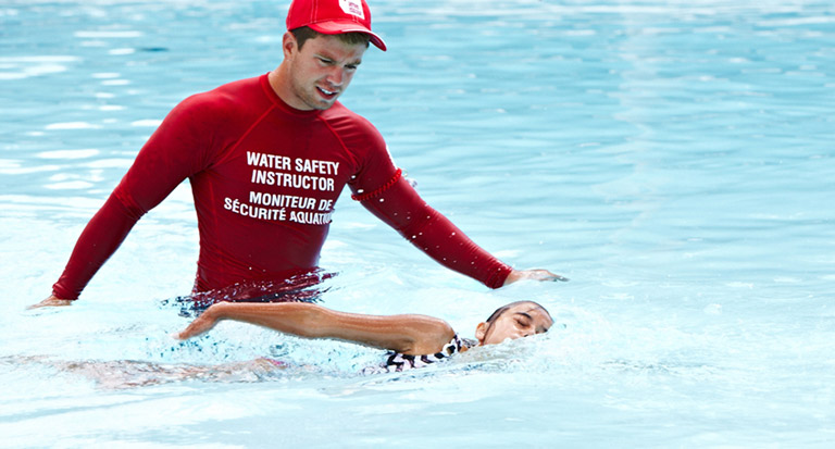 A Red Cross Water Safety Instructor looks on as a student does a front stroke in the pool.