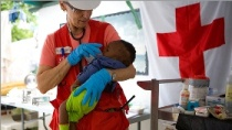 Red Cross international aid delegate tending to infant