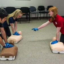 CPR instructor practicing with two students