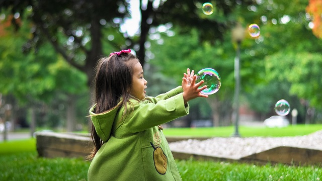 Toddler girl outside reaching for bubble