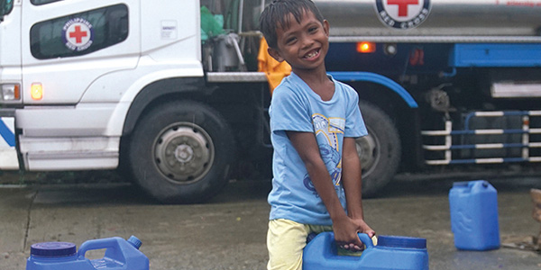 A small boy smiles at the camera as he carries a large blue water jug. a