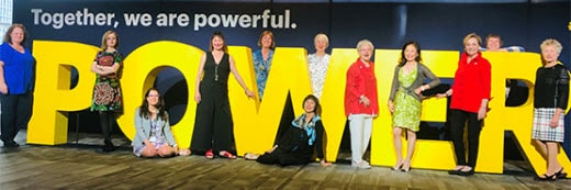 12 women standing in front of POWER sign