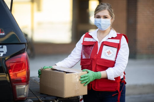 Red Cross worker with box assisting in COVID-19 response