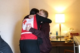 red cross volunteer hugs family facing floods two years in a row