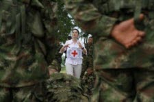 Red Cross worker in front of soldiers