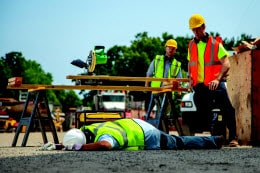 Two construction workers look and one injured colleague