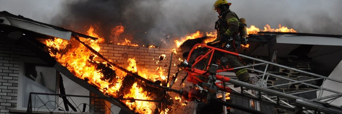 A firefighter on a ladder putting out a fire in a building
