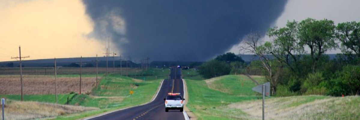 An emergency vehicle drives along a road towards a tornado