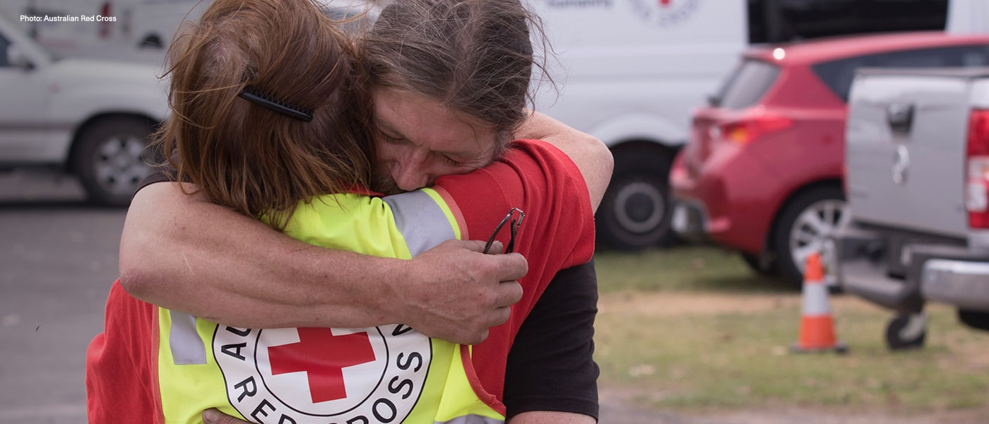 A man hugging a Red Cross volunteer