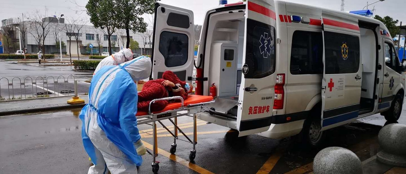 Chinese Red Cross workers help a patient into an ambulance