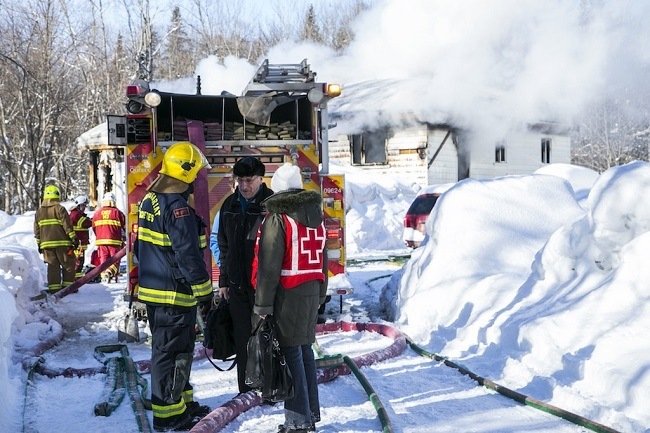 Firefighter talks to Canadian Red Cross responder following a house fire