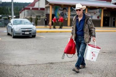 Everett Lightfoot walks with his cleanup kit