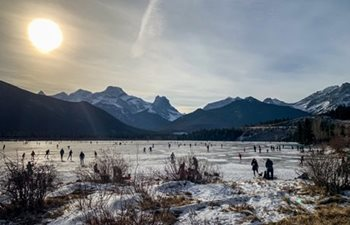 A frozen lake with people skating on it.