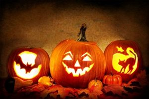 Three jack-o-lanterns sitting beside uncarved pumpkins