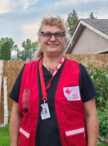 A woman stands in her backyard, wearing reading glasses and a bright red Red Cross vest, smiling.