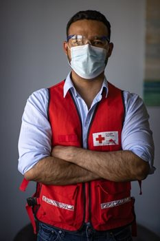 Wilson Restrepo, a psychiatrist, standing arms crossed in a Red Cross vest, and mask and goggles.
