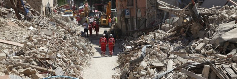 Rubble from demolished buildings and rescue workers walking along the road.