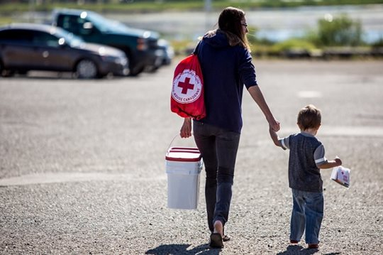 A mother carries a Canadian Red Cross care kit while walking holder her sons hand