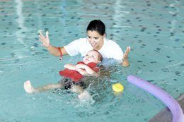 Child floating in pool at a Red Cross Swim Preschool class