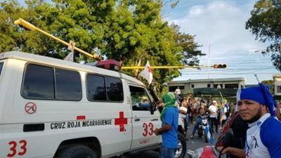 A Red Cross ambulance in a crowded area