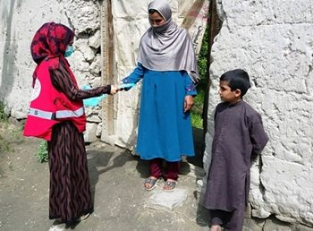 A member of the Afghan Red Crescent handing material to a woman with a young child.