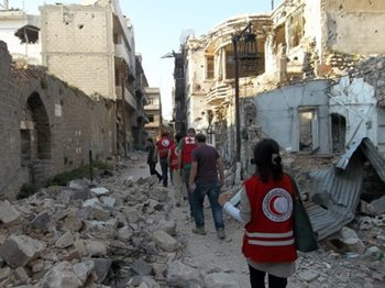 Red Crescent members walking through a destroyed street in Syria.