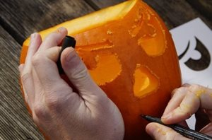 Hands carving a face into a pumpkin
