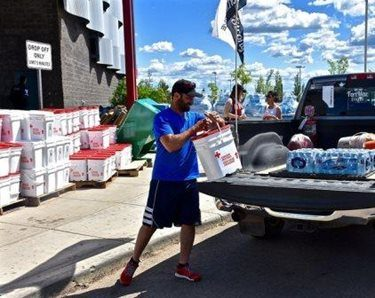 A man loads clean-up supplies in a truck after re-entering Fort McMurray