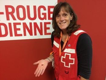 Manon Michaud, Canadian Red Cross volunteer, holding one of Aileen's glass hearts