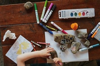 Paints and markers on a table with child's hands drawing on a rock