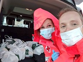 A man and a woman wearing medical masks pose with bags of groceries. The woman wears a red cross jacket.