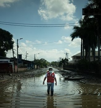 A Red Cross member walking down a flooded street