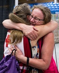 Canadian Red Cross volunteer hugs a woman