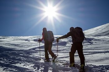 Two people snowshoeing over a snow-covered hill