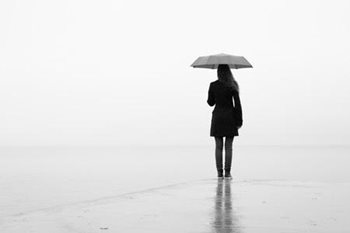 A woman walking alone with an umbrella