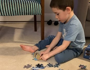 A boy sitting on the floor playing with a puzzle