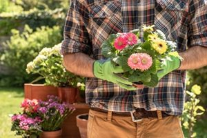 A man in gardening gloves holding flowers